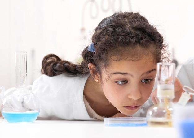 Kleines mädchen macht ein wissenschaftliches experiment in der schule experiment