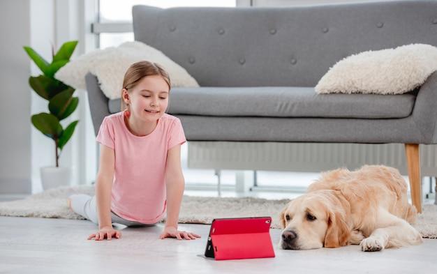Kleines mädchen macht stretching mit online-yoga-lektionen auf dem tablet und bleibt mit golden retriever hund auf dem boden
