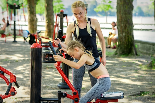 Kleines mädchen macht übungen auf simulator unter aufsicht der jungen trainerin im park