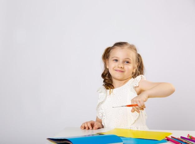 Kleines mädchen macht unterricht, zeichnet, lächelt
