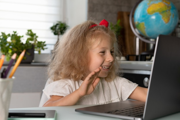 Kleines mädchen macht unterricht zu hause an einem laptop-online-training-videokommunikation