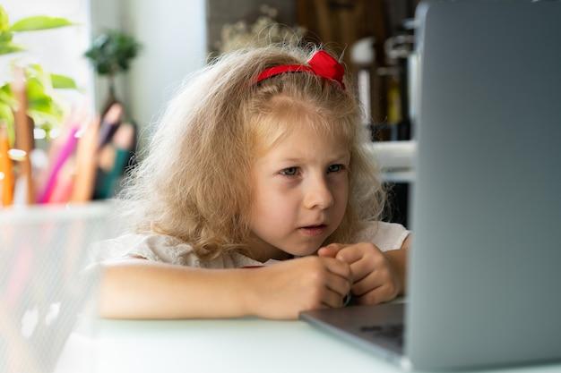 Kleines mädchen macht unterricht zu hause an einem laptop schreibt mit einem stift in einem notizbuch