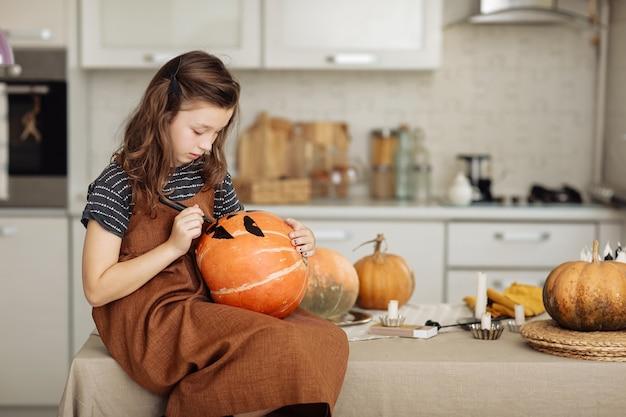 Kleines mädchen malt einen kürbis für halloween-vorbereitung für halloween