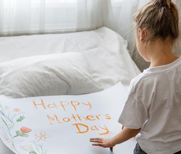 Kleines mädchen malt grußkarte für mama mit der aufschrift glücklicher muttertag und blumen.