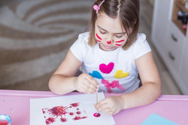Kleines mädchen malt mit ihren händen und fingern zu hause