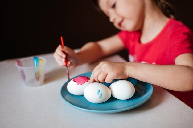 Kleines mädchen malt ostereier auf blauem teller, der am selektiven fokus des tisches sitzt