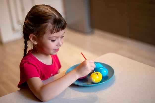 Kleines mädchen malt ostereier auf blauem teller, der am tisch in der küche sitzt