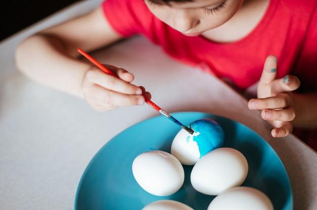 Kleines mädchen malt ostereier auf blauem teller, der am tisch sitzt