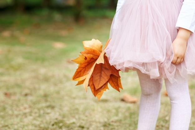 Kleines mädchen mit ahornblatt am herbstpark.