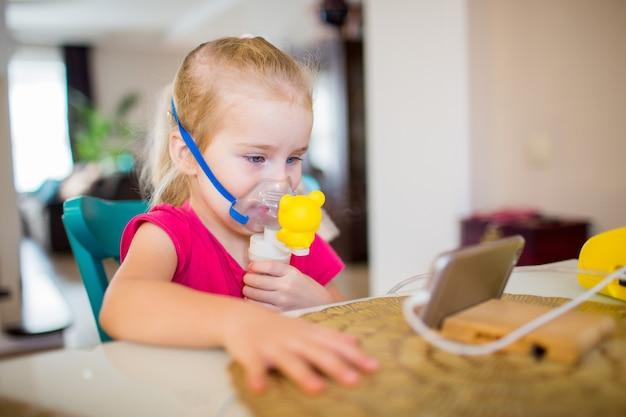Kleines mädchen mit allergischem asthma unter verwendung des inhalators und der aufpassenden karikaturen auf einem smartphone. mädchen atmet medizin durch eine zerstäubermaske ein. behandlung der atemwege.