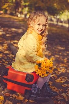 Kleines mädchen mit blondem haar im herbsthintergrund mit blumen und koffer