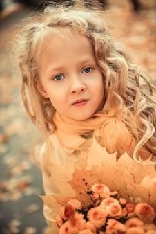Kleines mädchen mit blondem haar im herbsthintergrund mit gelben blumen