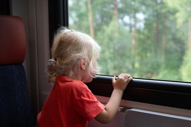 Kleines mädchen mit blonden haaren, das mit dem zug reist. mädchen schaut durch fenster. öffentliche verkehrsmittel und nahverkehrskonzept