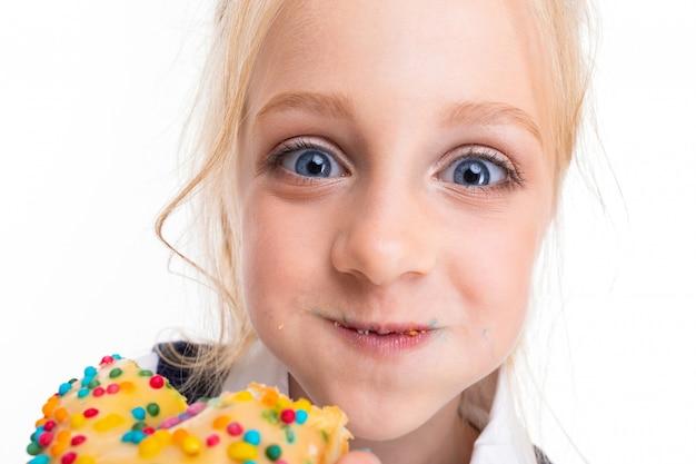 Kleines mädchen mit blonden haaren, die mit pferdeschwanz gefüllt sind, großen blauen augen und süßem gesicht isst helle donuts, die mit glasur bedeckt sind