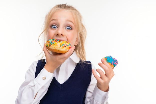 Kleines mädchen mit blonden haaren, die mit pferdeschwanz gefüllt sind, großen blauen augen und süßem gesicht mit hellen donuts, die mit glasur bedeckt sind