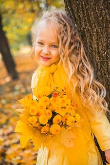 Kleines mädchen mit blonden haaren im herbst mit gelben blumen