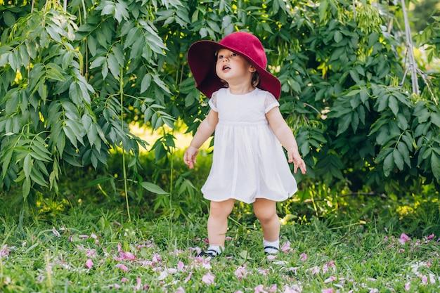 Kleines mädchen mit blonden haaren in einem weißen kleid und dem roten hut der mutter im sonnigen sommertag des parks
