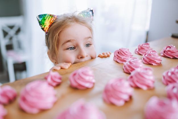Kleines mädchen mit blonden haaren und blauen augen schauen auf köstliche hausgemachte rosa marshmallows ot zephyr auf tisch in der küche.