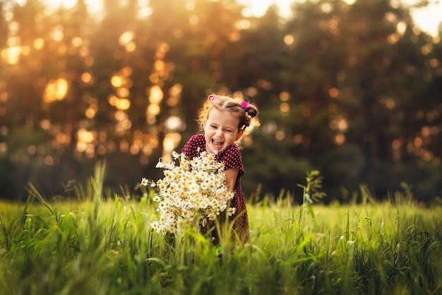 Kleines mädchen mit blumen auf natur im sommer