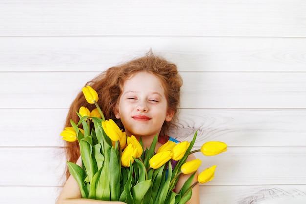 Kleines mädchen mit blumenstrauß tulpen.