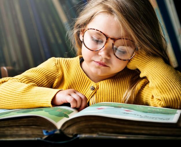 Kleines mädchen mit brille, das eine geschichte liest