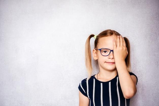 Kleines mädchen mit brille, das ihr auge mit der hand bedeckt, während sie einen sehtest vor der schule, dem kindergarten und der schulmedizinischen untersuchung macht