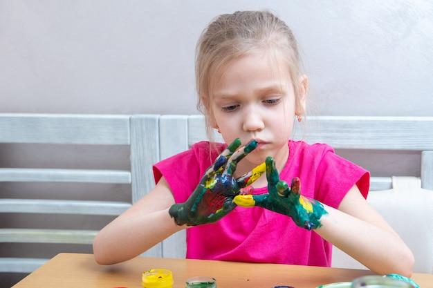 Kleines mädchen mit bunt bemalten händen. ein mädchen schmiert sich konzentriert farbe auf die hände und betrachtet das ergebnis.