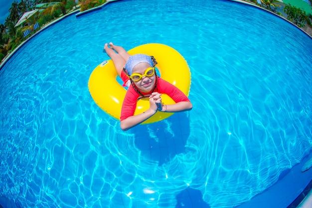 Kleines mädchen mit dem aufblasbaren gummikreis, der spaß im swimmingpool hat