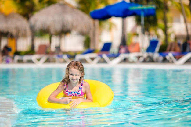 Kleines mädchen mit dem aufblasbaren gummikreis, der spaß im swimmingpool im freien im luxushotel hat