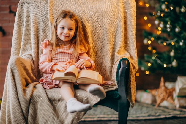 Kleines mädchen mit dem buch, das im stuhl durch weihnachtsbaum sitzt