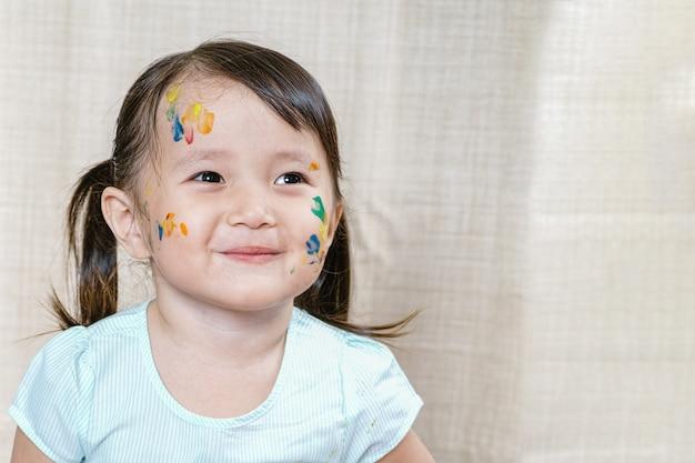 Kleines mädchen mit dem bunten schmutz gemalt auf ihrem gesicht.
