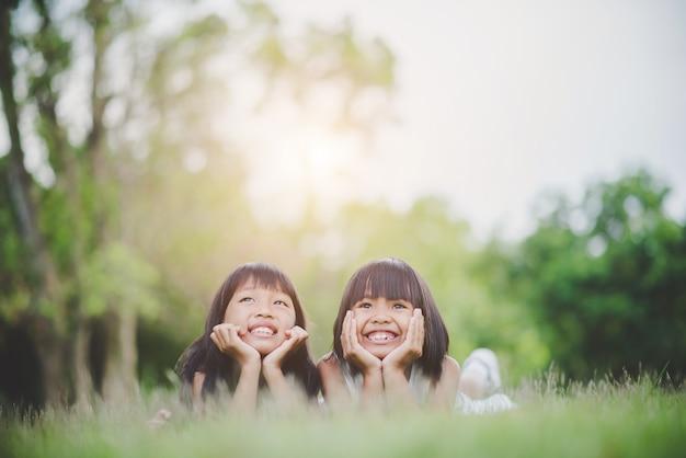 Kleines mädchen mit dem freund, der bequem auf dem gras und dem lächeln liegt