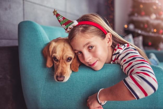 Kleines mädchen mit dem gelben hund, der auf sofa aufwirft