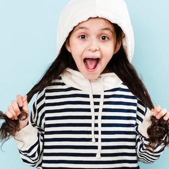 Kleines mädchen mit dem hoodie, der mit dem haar spielt