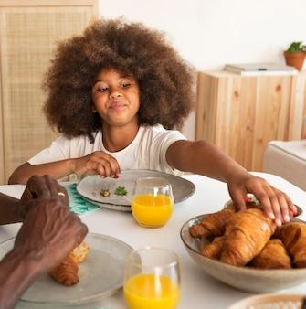 Kleines mädchen mit dem lockigen haar, das frühstück isst
