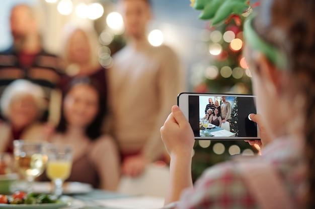 Kleines mädchen mit dem smartphone, das foto der großen glücklichen familie nimmt, die durch bedienten tisch für weihnachtsessen zu hause gesammelt wird