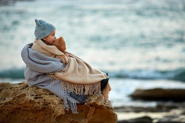 Kleines mädchen mit dem teddybären, der auf strand sitzt