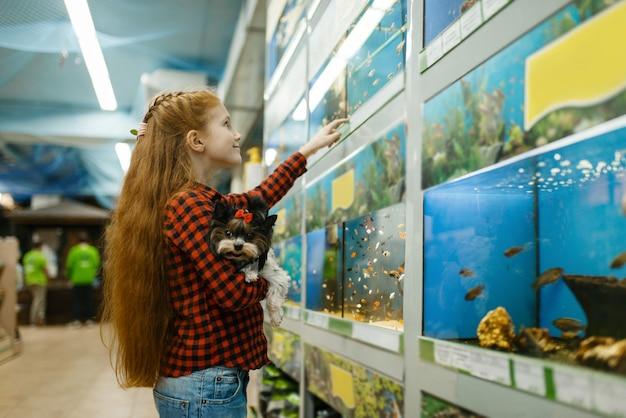 Kleines mädchen mit dem welpen, der auf fischen im aquarium schaut