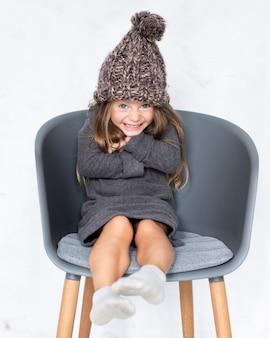 Kleines mädchen mit dem winterhut, der auf stuhl sitzt