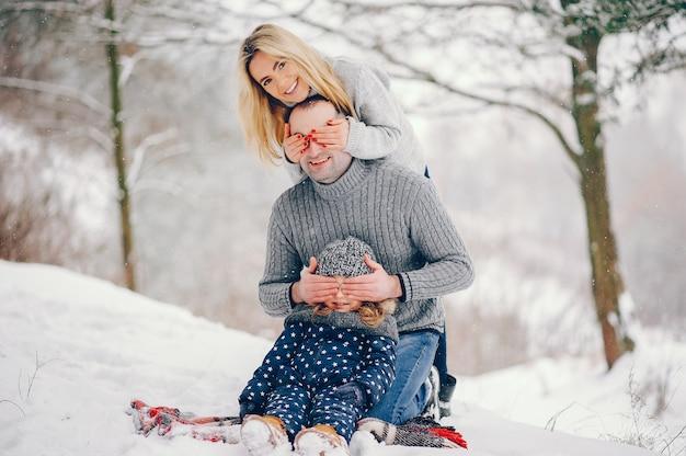 Kleines mädchen mit den eltern, die auf einer decke in einem winterpark sitzen