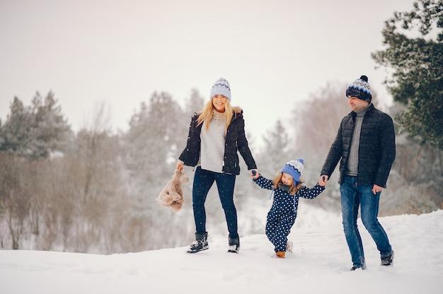 Kleines mädchen mit den eltern, die in einem winterpark spielen