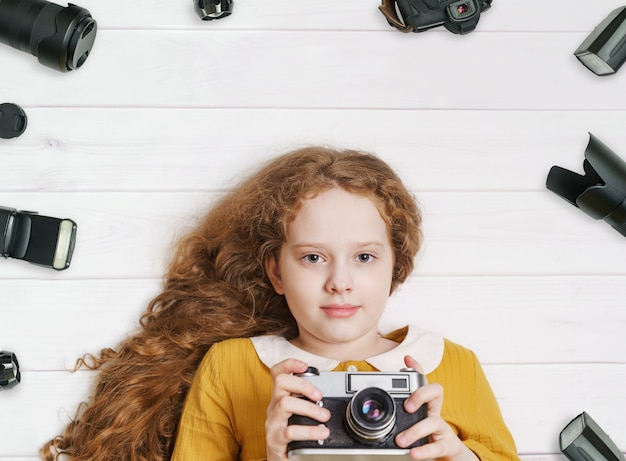 Kleines mädchen mit den retro- fotokameras und fotozubehör, die auf einem bretterboden liegen.