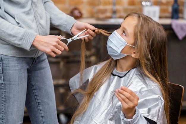 Kleines mädchen mit der medizinischen maske, die einen haarschnitt bekommt