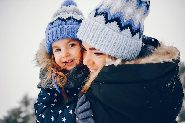 Kleines mädchen mit der mutter, die in einem winterpark spielt