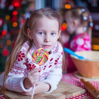 Kleines mädchen mit der süßigkeit, die weihnachtskuchen zubereitet