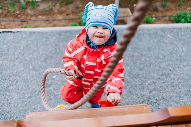 Kleines mädchen mit down-syndrom spielt auf dem spielplatz, selektiver fokus