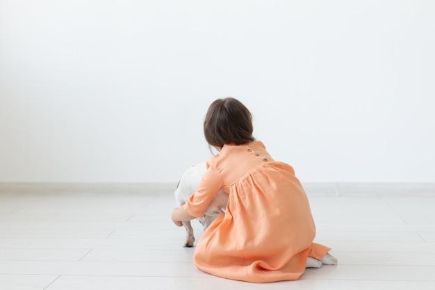 Kleines mädchen mit dunklen haaren spielt mit ihrem geliebten hund, während sie auf dem boden in einem pfirsichkleid gegen die oberfläche der weißen wand sitzt