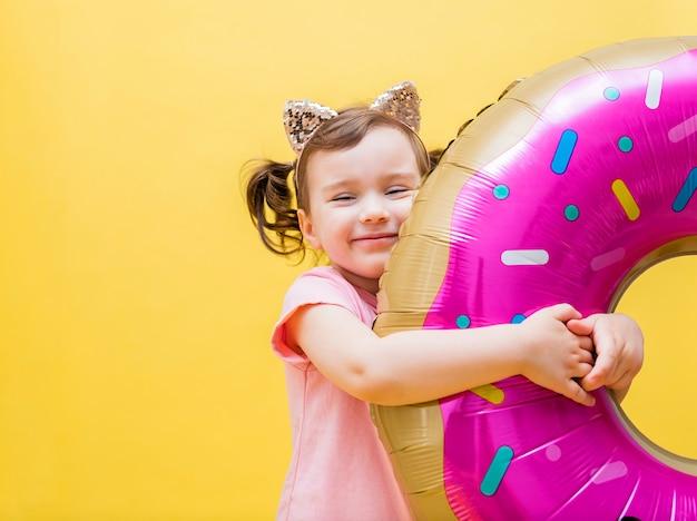 Kleines mädchen mit einem ballon auf einem gelben raum. nettes mädchen mit zöpfen mit einem ballon in form eines donuts. ballon donut. ein kleines mädchen sitzt und lächelt mit einem ballon. speicherplatz kopieren