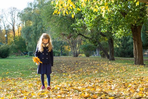 Kleines mädchen mit einem blumenstrauß von gelben ahornblättern