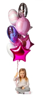 Kleines mädchen mit einem bündel luftballons, die lokal auf weißem hintergrund sitzen